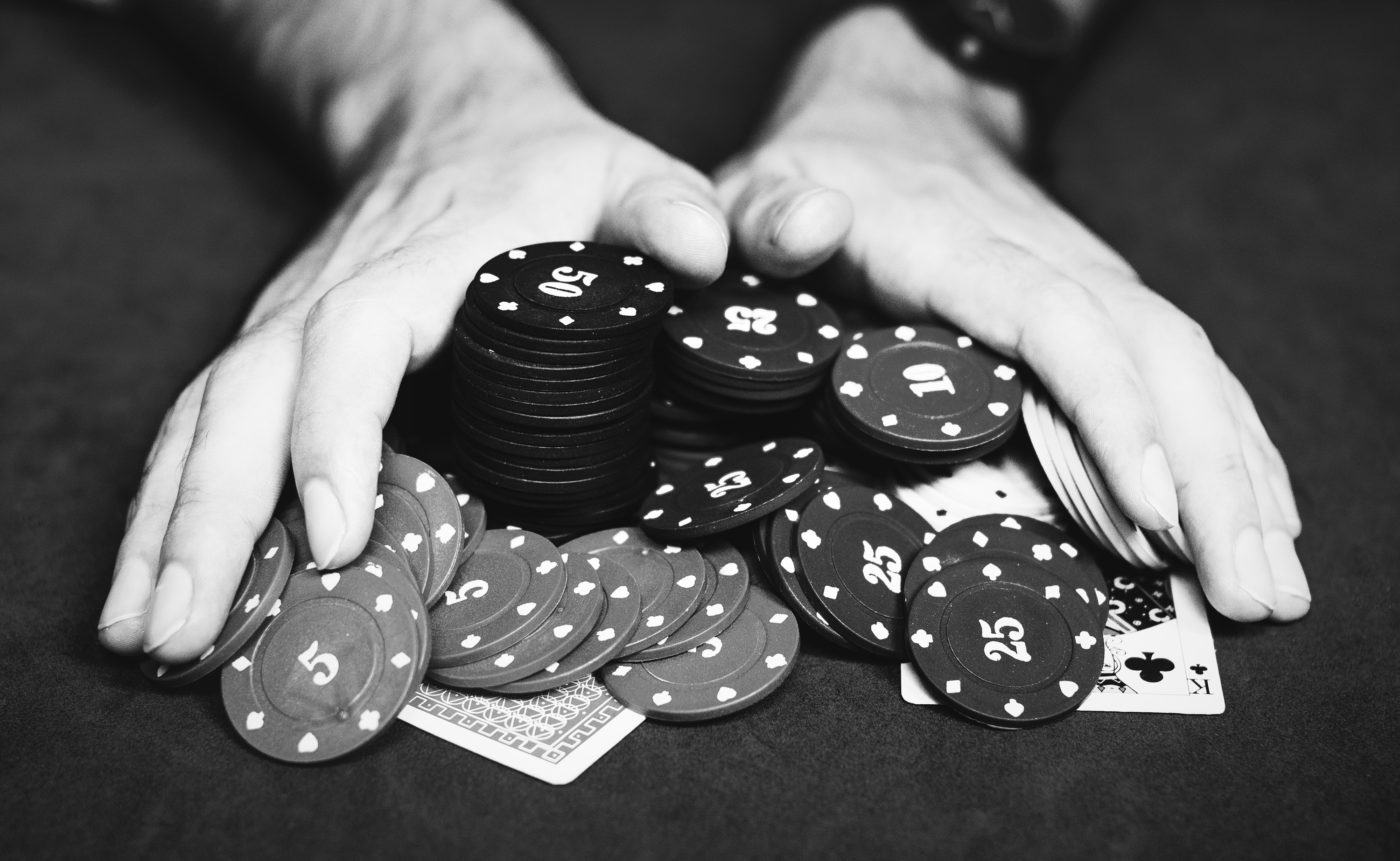 Photo of Hands Pushing Poker Chips Onto the Table