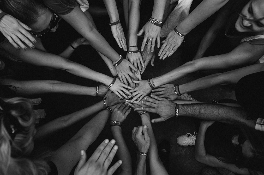 Photo of group of people huddling and putting their hands in the circle
